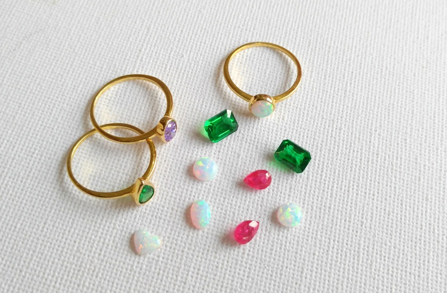 Emeralds, rubies and white opal gemstones waiting to be set into stackable rings.